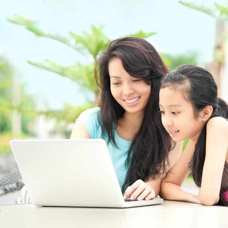 mom sitting with daughter while doing online registration for before and after care program
